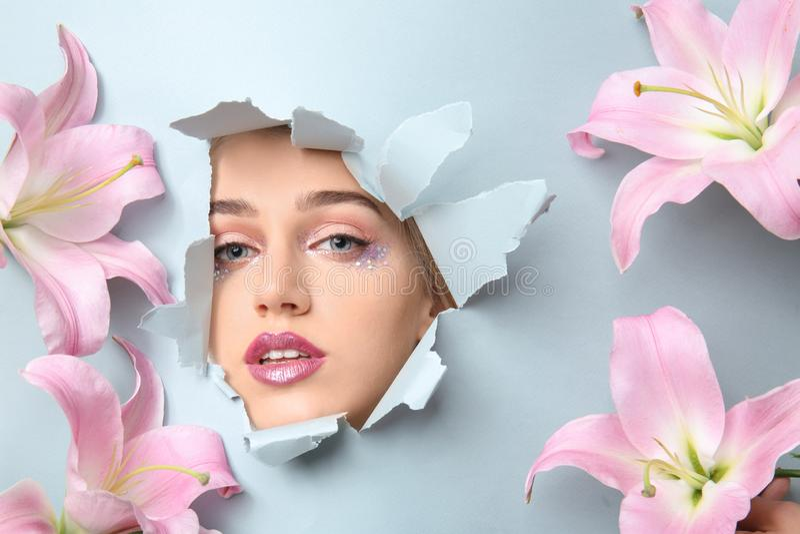 Schöne Blumen und Gesicht des sichtbaren durchgehenden Lochs der jungen Frau in heftigem Farbpapier stockfotos