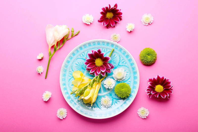 Schöne Blumen und Platte auf rosa Hintergrund, obenliegende Ansicht stockbild