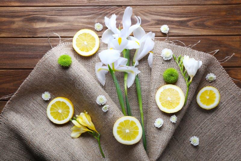Schöne Blumen und Zitronenscheiben mit Leinwand auf hölzernem backgro stockfoto