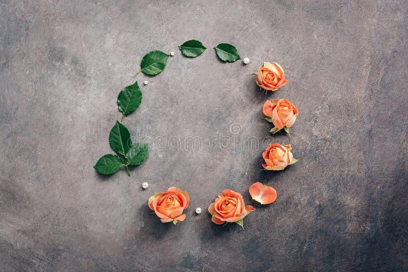 Schöne Blumenzusammensetzung, ein runder Rahmen von den korallenroten Rosen verziert mit Perlenperlen auf einem dunklen strukturi stockfotografie
