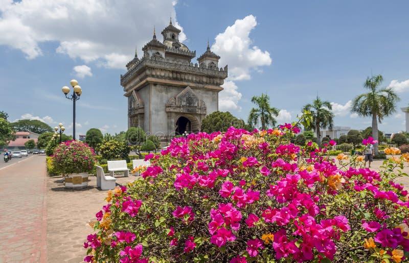 Schöne Bouganvillaanlage mit Victory Gate Patuxai im Hintergrund in der Mitte von Vientiane, Laos stockbilder