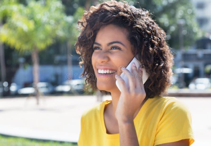 Schöne brasilianische Frau, die über Telefon lacht stockfotos