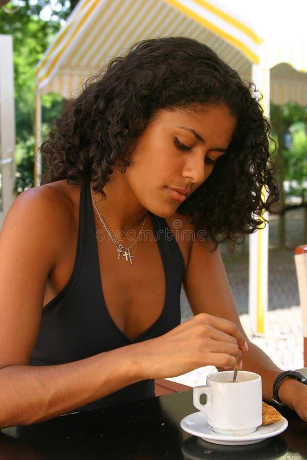 Schöne brasilianische Frau, die einen Kaffee trinkt lizenzfreie stockfotos
