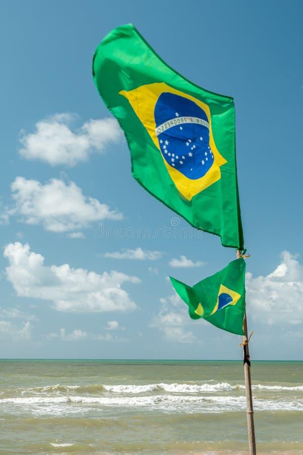 Schöne brasilianische Nationalflagge in einem blauen Himmelstag stockbild