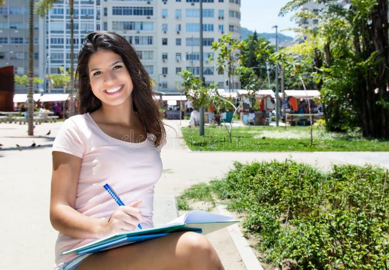 Schöne brasilianische Studentin, die draußen lernt lizenzfreie stockbilder