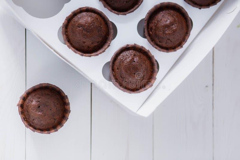 Schöne braune köstliche Schokoladenmuffins in einer Lieferungsnahrung des weißen Kastens auf hölzerner Hintergrundnahaufnahme lizenzfreies stockfoto