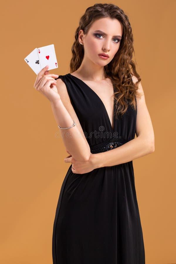 Schöne braunhaarige Frau, die zwei Asse als Zeichen für Pokerspiel, das Spielen und Kasino hält lizenzfreies stockfoto