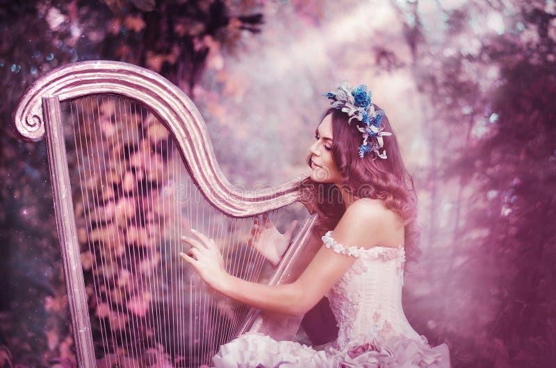 Schöne braunhaarige Frau mit einem Blumenkranz auf ihrem Kopf, ein weißes Kleid tragend, welches die Harfe im Wald spielt lizenzfreie stockbilder