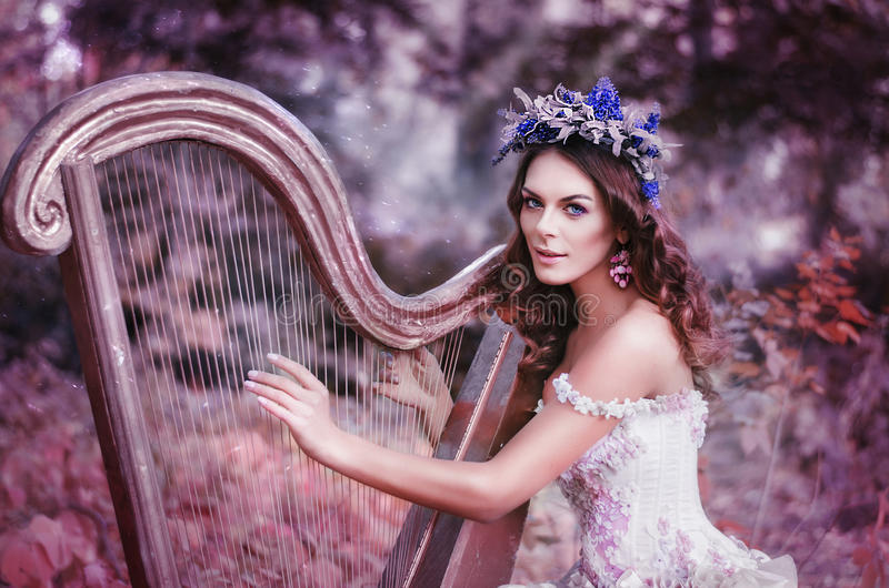 Schöne braunhaarige Frau mit einem Blumenkranz auf ihrem Kopf, ein weißes Kleid tragend, welches die Harfe im Wald spielt lizenzfreie stockfotos