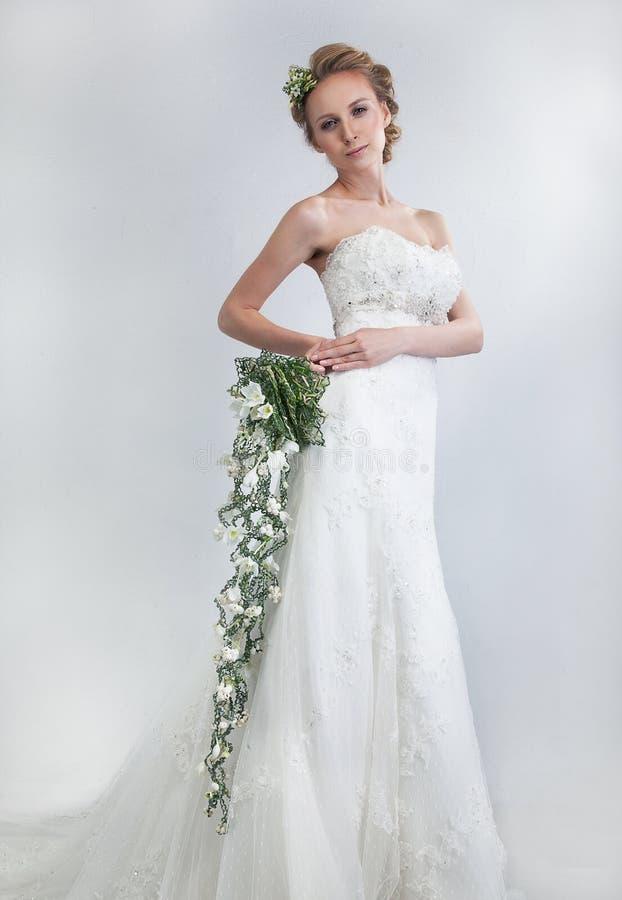 Schöne Braut blond mit Blumenblumenstrauß stockbild