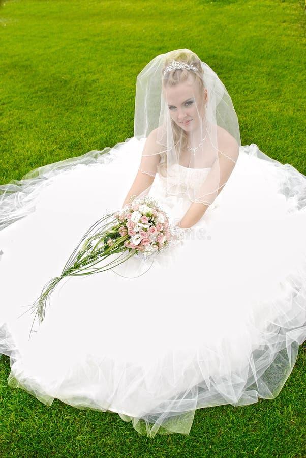 Schöne Braut, die beim wedding am Gras aufwirft stockbild