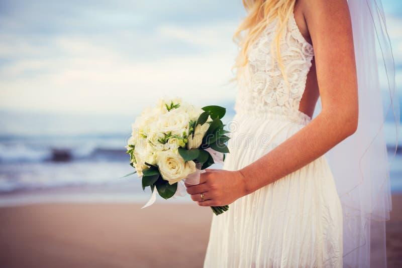 Schöne Braut, die den Strand bei Sonnenuntergang bereitsteht stockbild