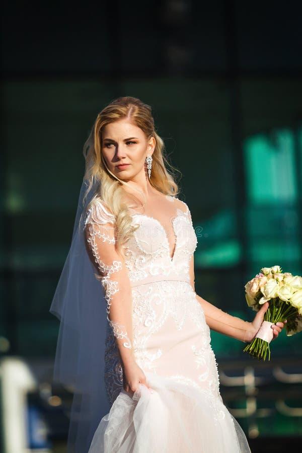 Sch?ne Braut, die einen Rock ihres Kleides h?lt und Blumenstrau? heiratet stockfoto
