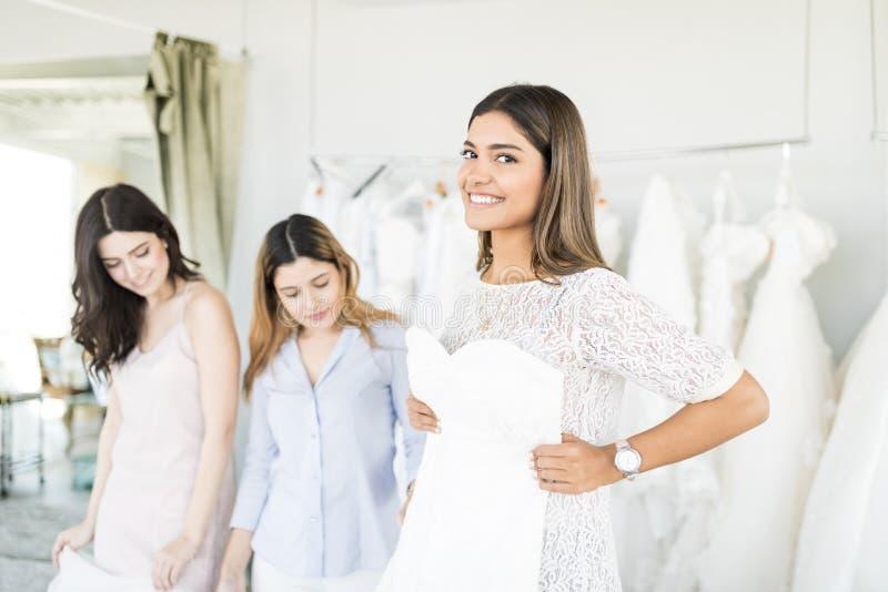 Schöne Braut, die ihr Heirat-Kleid im Geschäft kauft lizenzfreies stockbild