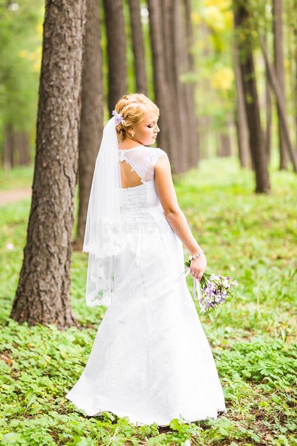 Schöne Braut, die in ihrem Hochzeitstag aufwirft lizenzfreie stockbilder