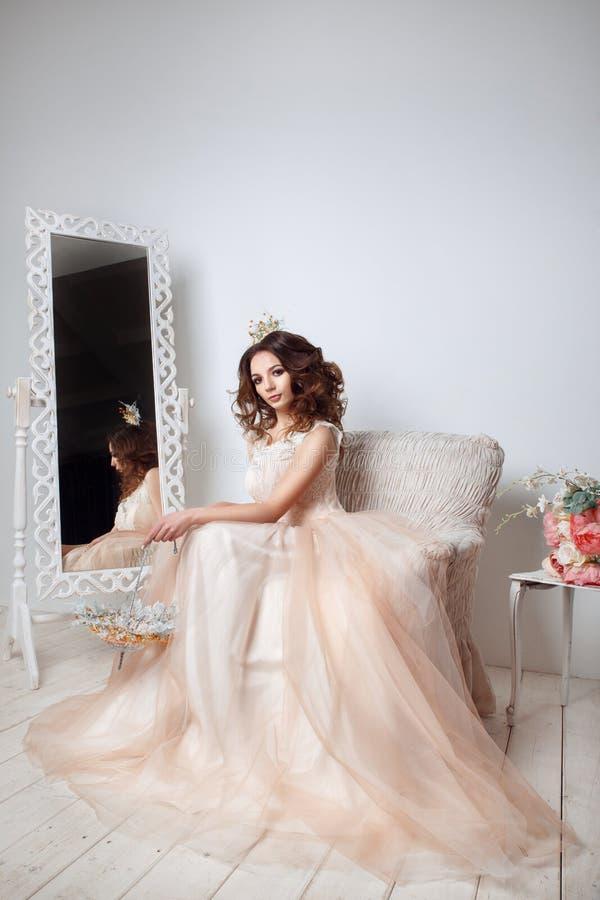Schöne Braut, die im Pfirsichhochzeitskleid sitzt auf Sofa in einem weißen Foto Studio aufwirft stockbilder