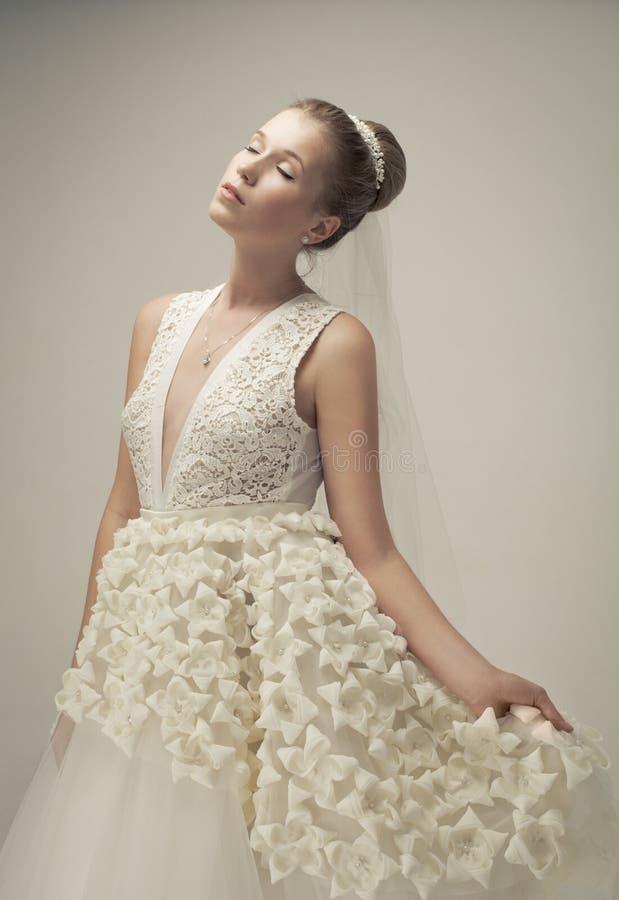 Schöne Braut, die luxuriöses Hochzeitskleid trägt stockfotografie