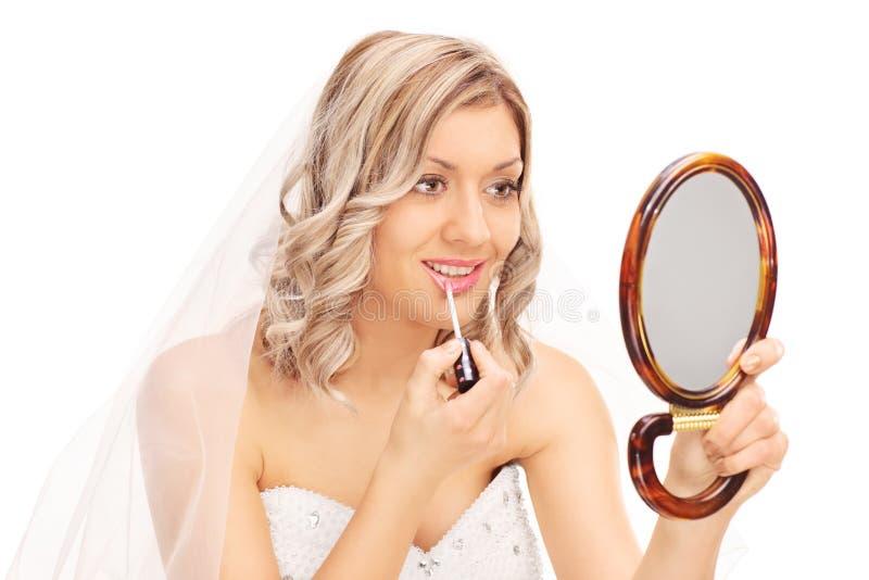 Schöne Braut, die Make-up anwendet stockfotos