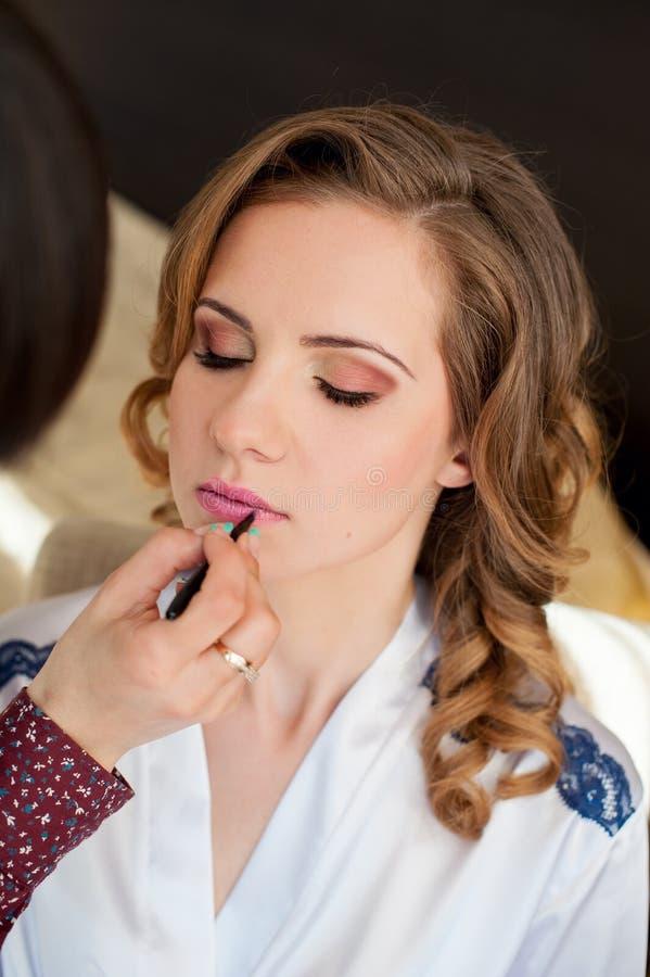 Schöne Braut, die morgens Hochzeitsmake-up tut lizenzfreie stockfotografie