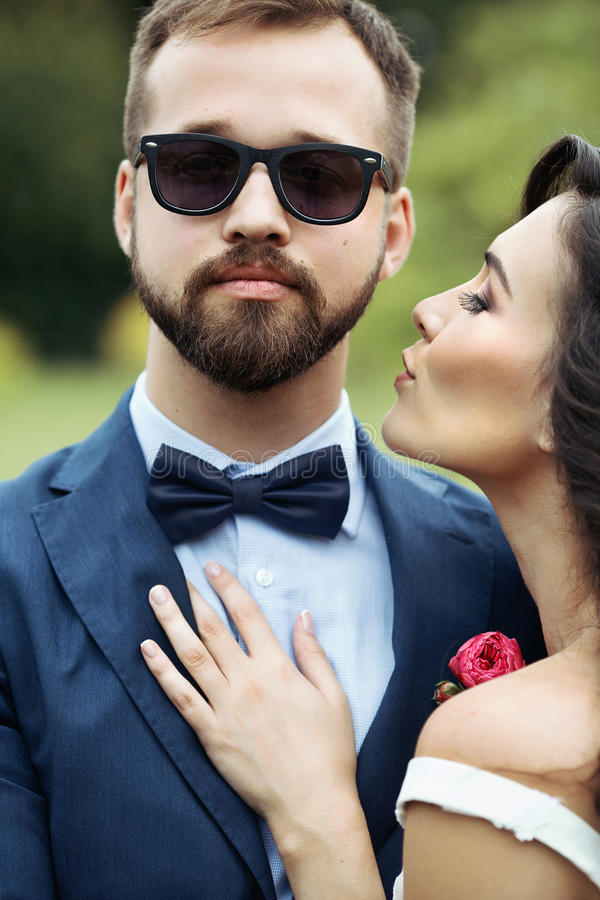 Schöne Braut, die sich herein lehnt, um hübschen überzeugten Bräutigam in s zu küssen lizenzfreie stockfotos