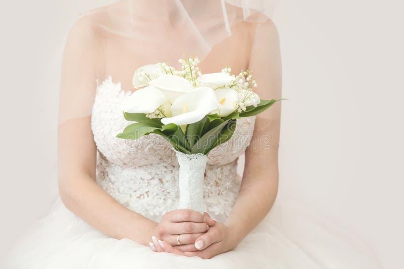 Schöne Braut in einem Heiratskleid, das einen Blumenstrauß des weißen Zantedeschia hält Weißer Hintergrund stockfotos