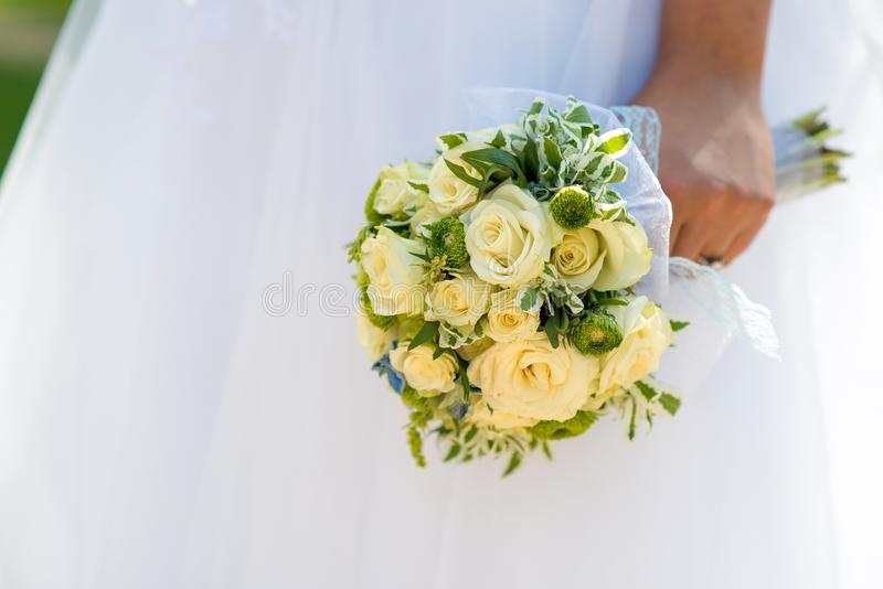Schöne Braut in einem Heiratskleid, das einen Blumenstrauß von gelben Rosen hält Weißer Hintergrund lizenzfreie stockfotos