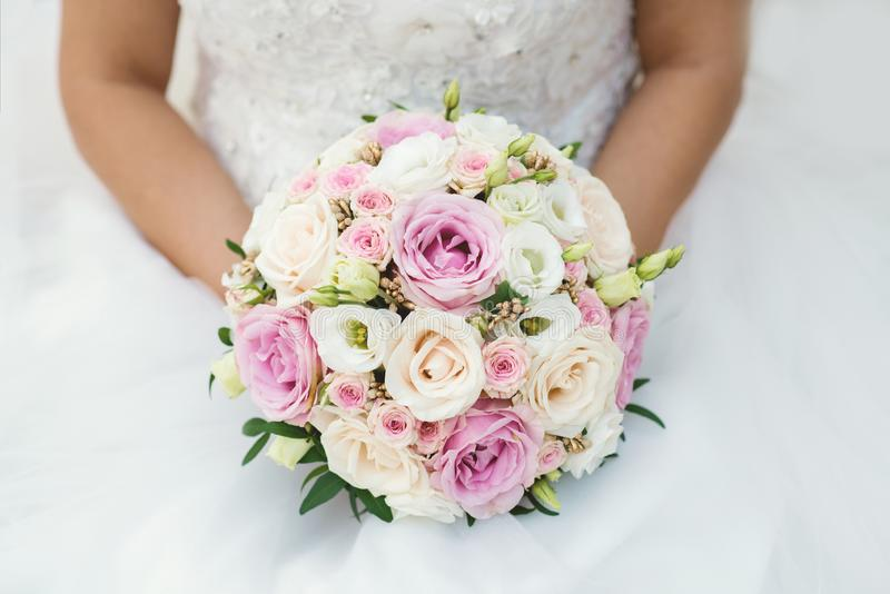 Schöne Braut in einem Heiratskleid, das einen Blumenstrauß von rosa Rosen hält Weißer Hintergrund stockfotos