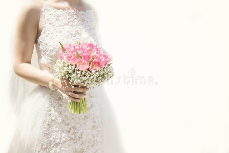 Schöne Braut in einem Heiratskleid, das einen Blumenstrauß von rosa Tulpen hält Weißer Hintergrund stockbilder