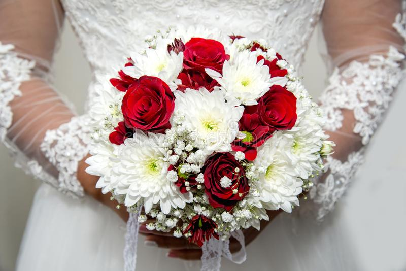 Schöne Braut in einem Heiratskleid, das einen Blumenstrauß von roten Tulpen hält Weißer Hintergrund lizenzfreie stockfotografie