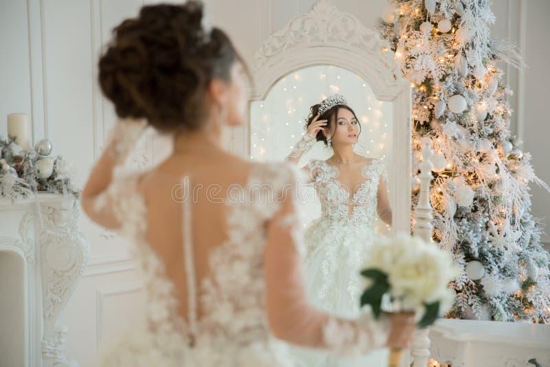 Schöne Braut in einem Hochzeitskleid an einem Spiegel im Weihnachten Gir lizenzfreie stockfotos