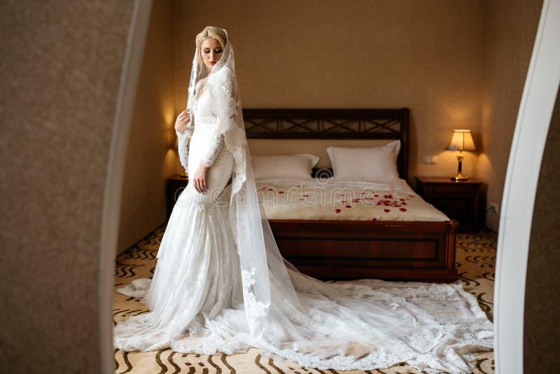 Schöne Braut in einem Spitzehochzeitskleid und in einem langen Schleier, die im Hotelzimmer stehen stockfotografie
