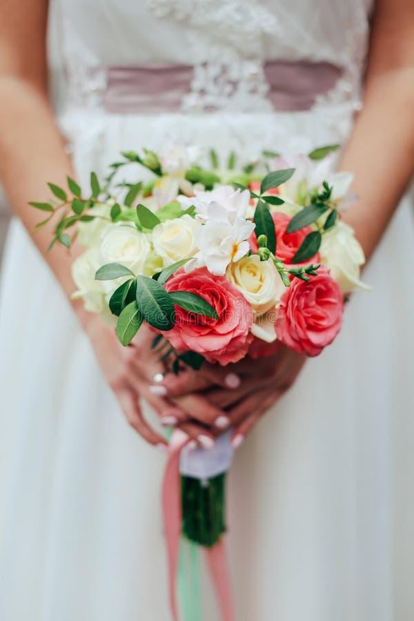 Schöne Braut hält einen bunten Blumenstrauß der Hochzeit Schönheit von farbigen Blumen Nahaufnahmebündel Florets lizenzfreie stockfotografie