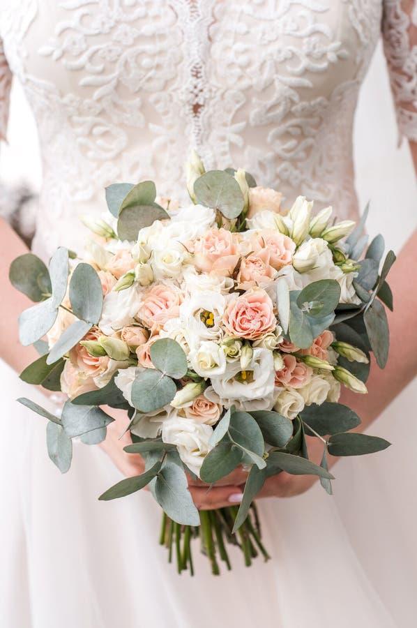 Schöne Braut hält einen bunten Blumenstrauß der Hochzeit Schönheit von farbigen Blumen Nahaufnahmebündel Florets Brautzubehör f stockfotos