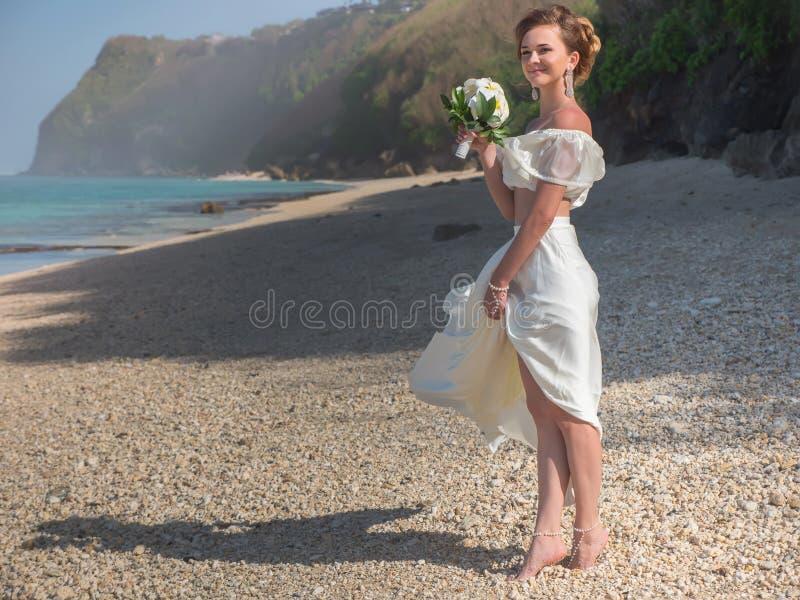 Schöne Braut heiratete am Strand, Bali Die Braut mit einer Blume lizenzfreie stockfotografie