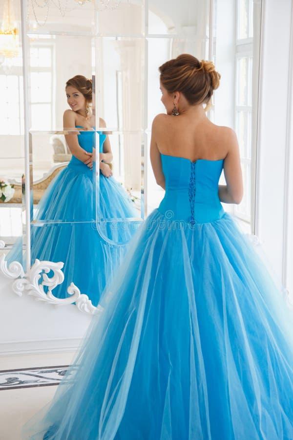 Schöne Braut in herrlicher blauer Kleid-Aschenputtel-Art nahe Spiegel stockfoto