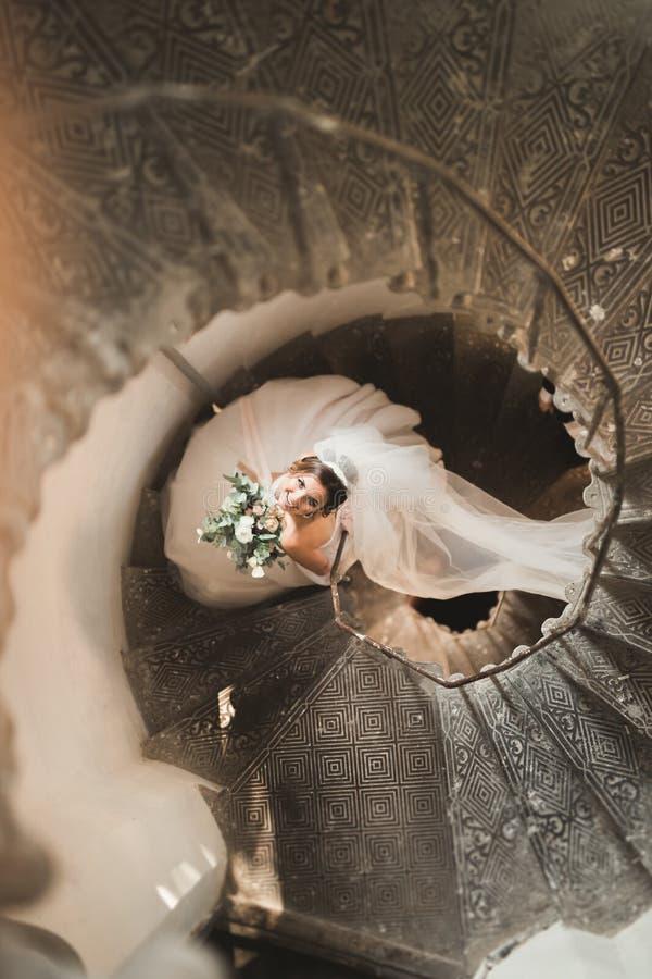 Schöne Braut im ausgezeichneten Kleid steht allein auf Treppe stockfotos