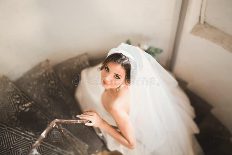 Schöne Braut im ausgezeichneten Kleid steht allein auf Treppe stockbild