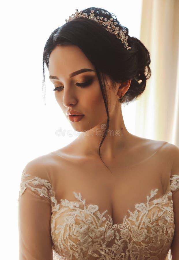 Schöne Braut im eleganten Hochzeitskleid und Diadem, das in r aufwirft stockbilder