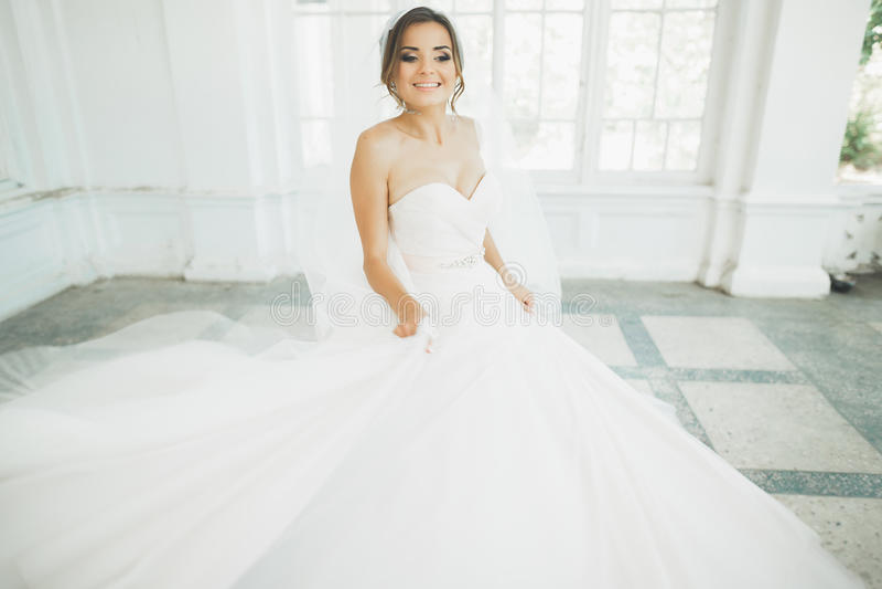 Schöne Braut im Hochzeitskleid mit langem Tellerrock, weißem Hintergrund, Tanz und Lächeln lizenzfreies stockfoto