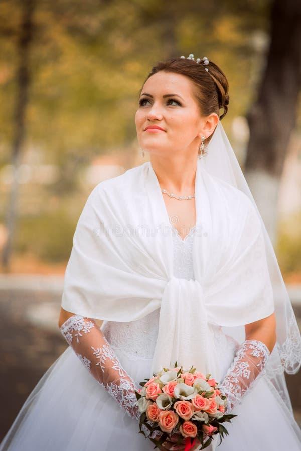 Schöne Braut im Hochzeitskleid und im Brautblumenstrauß, glückliche Jungvermähltenfrau mit Hochzeitsblumen, Frau mit Hochzeitsmak lizenzfreies stockfoto