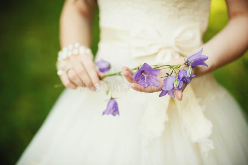 Schöne Braut im luxuriösen Hochzeitskleid mit purpurrotem Lavendelflorida stockbild