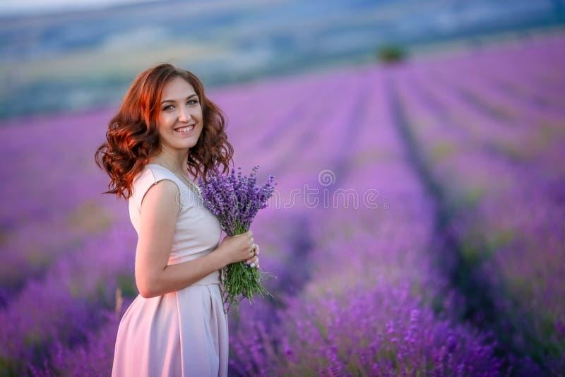 Schöne Braut im luxuriösen Hochzeitskleid im purpurroten Lavendel blüht Romantische stilvolle Frau der Mode mit Veilchen stockfoto