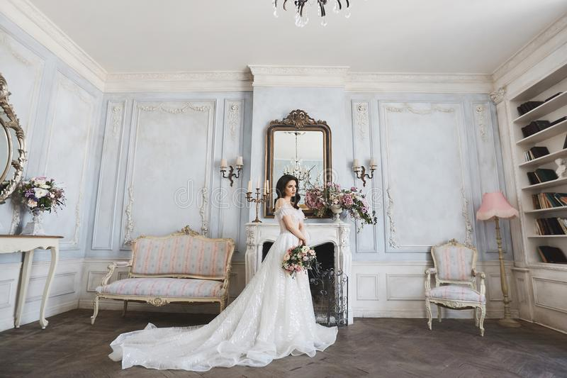 Schöne Braut, junge vorbildliche Brunettefrau, im stilvollen Hochzeitskleid mit nackten Schultern, mit Blumenstrauß von Blumen he stockfotos