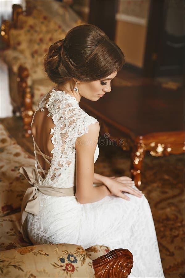 Schöne Braut, junge vorbildliche Brunettefrau, im stilvollen Hochzeitskleid mit nackter Rückseite sitzt auf dem Weinlesesofa und  stockbild
