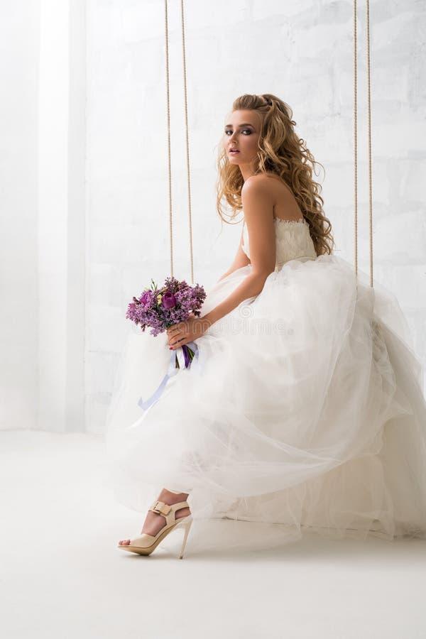Schöne Braut mit Blumenstrauß auf einem Schwingen im Studio lizenzfreies stockfoto