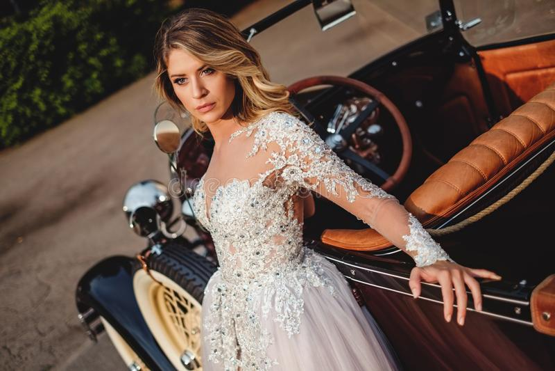 Schöne Braut mit der Haltung, die auf einem Oldtimer sich lehnt stockfoto