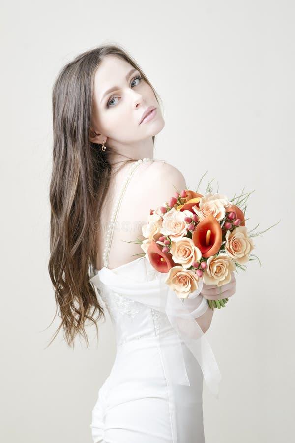 Schöne Braut mit der Heirat des orange Blumenstraußes stockbilder