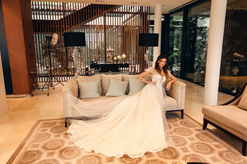 Schöne Braut mit dunklem Haar in elegantem Hochzeitskleid posiert in luxuriösem Interieur stockbild