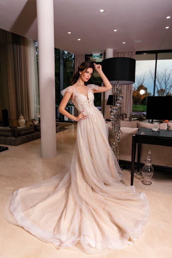 Schöne Braut mit dunklem Haar in elegantem Hochzeitskleid posiert in luxuriösem Interieur lizenzfreie stockfotos