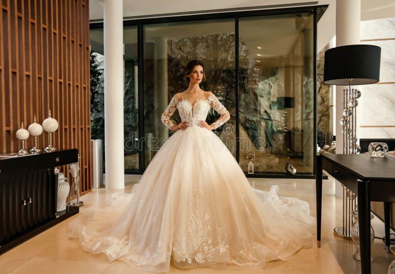 Schöne Braut mit dunklem Haar in elegantem Hochzeitskleid posiert in luxuriösem Interieur stockfotografie